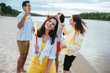 cheerful young woman holding sparkler and looking at camera while having fun on beach near multicultural friends