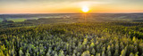 Fototapeta  - Drone photo of sunrise over forest in North Sweden - golden sun light with beams and shadows. Västerbotten, West Bothnia province, north of Sweden