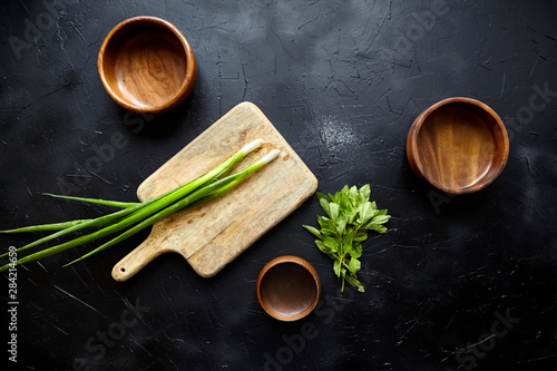 Obraz Cooking dinner. Cutting board and herb ingredients. Fresh mint leaves, scallion (green onion), empty natural wooden bowls on stone table, black background, top view, flat lay - fototapety do salonu