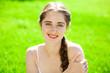 Leinwandbild Motiv Portrait of a young beautiful brunette woman in on summer park background