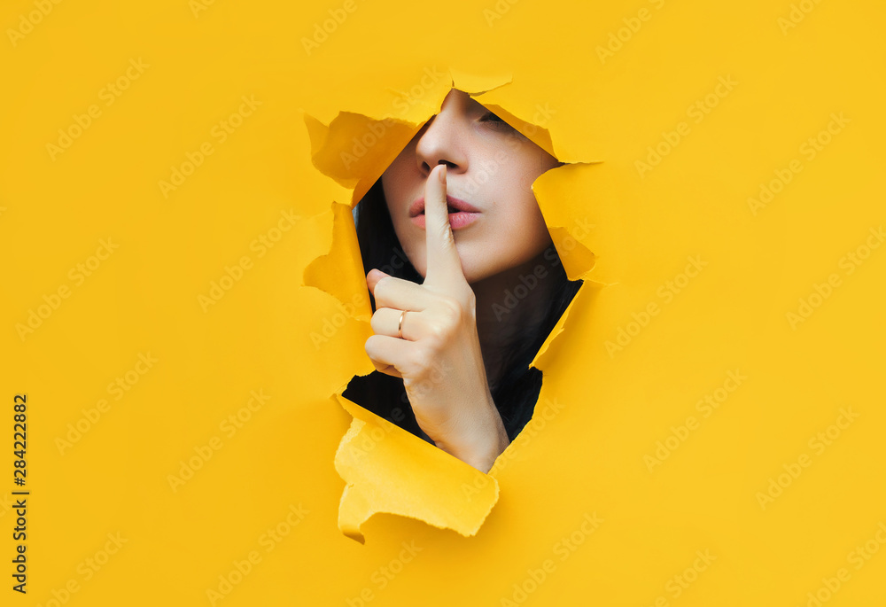 Fototapeta A young girl closes her lips with her index finger,making it clear to the viewer that you need to observe silence,keep a secret and not say too much. Censorship and harassment of freedom of speech.