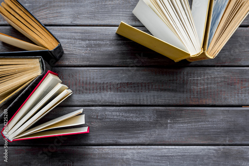 Books on library desk on wooden background top view space for text Canvas Print