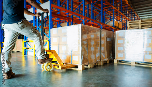 Stampa su Tela  warehouse worker working with hand pallet truck and cargo shipment pallet at distribution warehouse, stacked of package boxes on wooden pallet cargo export for transportation