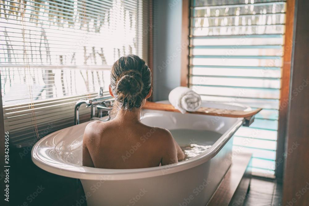 Fototapeta Luxury bath woman wellness spa relaxing soaking in warm water bathtub of hotel suite.
