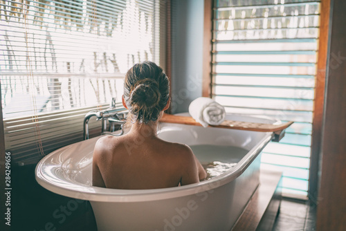 Leinwand Poster Luxury bath woman wellness spa relaxing soaking in warm water bathtub of hotel suite