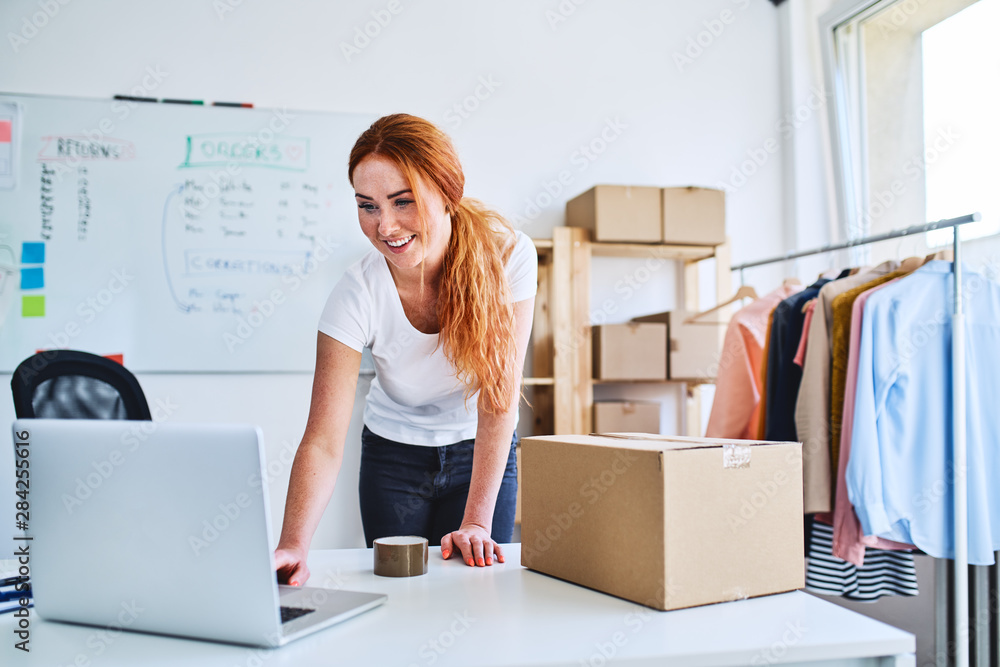 Fototapeta Young online business owner looking at laptop while preparing deliveries for clients