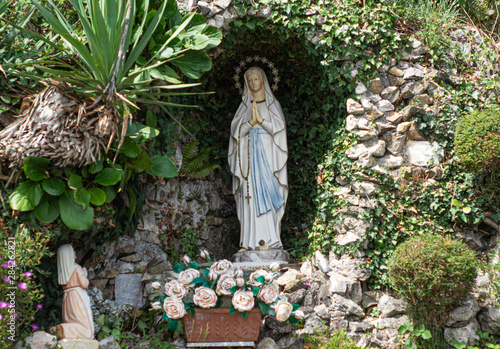 stone chapel with flowers and candles with Our Lady of Lourdes Canvas Print
