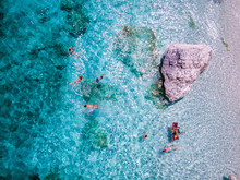 View From Above, Stunning Aerial View Of A Beautiful Beach Full Of Beach Umbrellas And People Sunbathing And Swimming On A Turquoise Water. Cala Gonone, Sardinia, Italy Orosei Coast