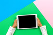 canvas print picture - Kid hands with tablet computer on pastel pink, blue and green background