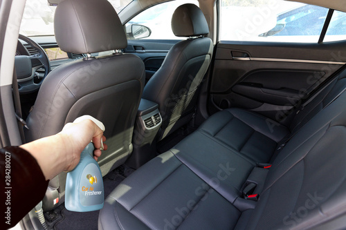 Fototapeta spraying fragrant deodorant inside the car obraz