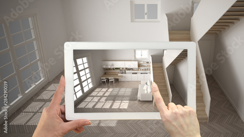 Fototapeta Augmented reality concept. Hand holding tablet with AR application used to simulate furniture and design products in empty interior with parquet floor, modern white kitchen, top view obraz