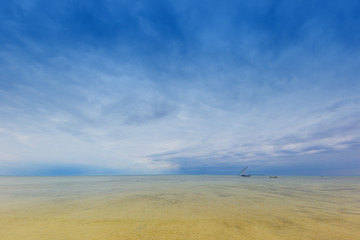 idylic outdoor scene with distant horizon calm ocean water and a dramatic clouded sky