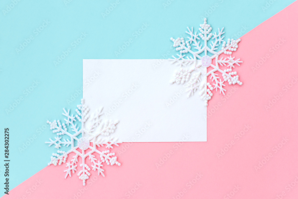 Fototapety, obrazy: White paper card decorated with snowflakes on pink and light blue background. New Year, Christmas and winter concept. Flat lay, top view, free copy space.
