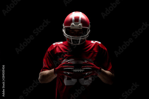 Fototapeta  American football player standing with rugby helmet and ball