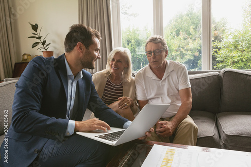 Photo  Active senior couple discussing with real estate agent over laptop in living roo