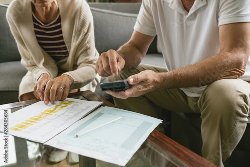 Pinturas sobre lienzo  Active senior couple calculating domestic bills on sofa in living room at comfor