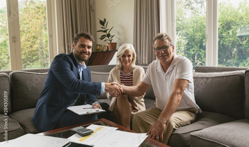 Fotomural  Active senior man shaking hands with real estate agent in living room
