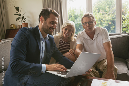 Active senior couple discussing with real estate agent over laptop in living roo Fototapete