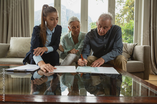 Cuadros en Lienzo Active senior couple signing an agreement with real estate agent over documents