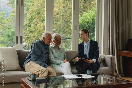 Fotomural  Active senior couple discussing with real estate agent over documents in living