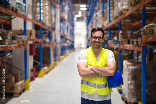 Obraz Portrait of middle aged warehouse worker standing in large warehouse distribution center with arms crossed. In background shelves with goods. - fototapety do salonu