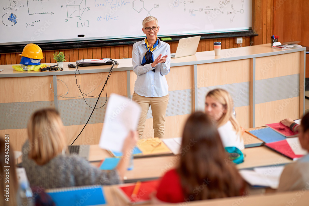 Fototapeta lecturer with students in an exam in a classroom.