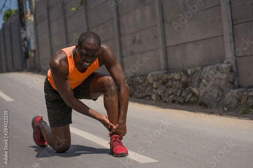 young athletic and fit black afro American runner in pain holding his ankle afte Wallpaper Mural