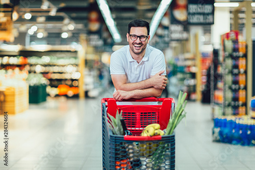 Fotomural  Handsome man shopping in supermarket pushing trolley and smilling