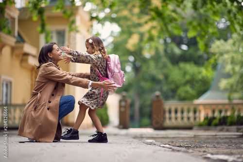 Obraz businessmom hugging her little gilr after school - fototapety do salonu