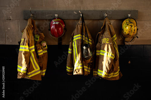 Dirty firefighter protection clothe and helmet hanging on the wall