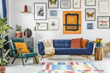 Green Armchair Next To Blue Settee In Colorful Living Room Inter