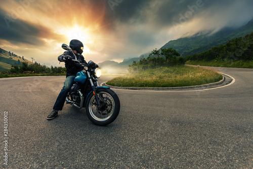 Fotografía  Motorcycle driver posing in Alpine landscape.