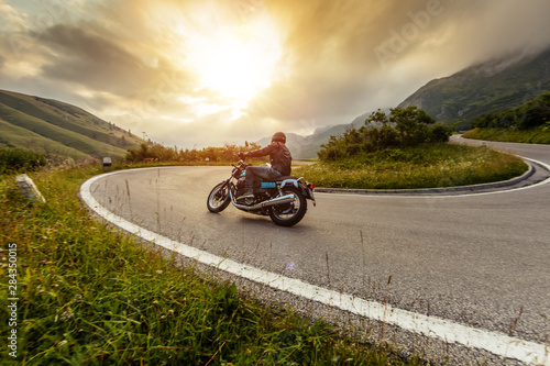 Motorcycle driver riding in Alpine landscape.