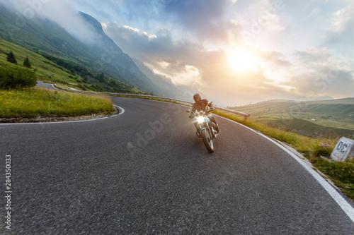 Fotografía Motorcycle driver riding in Alpine landscape.