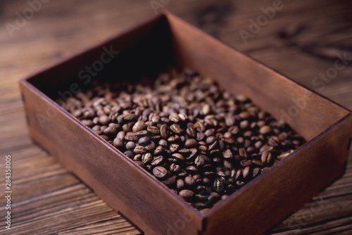 Tuinposter koffiebar natural coffee beans in a wooden box on a natural wooden background soft backlight