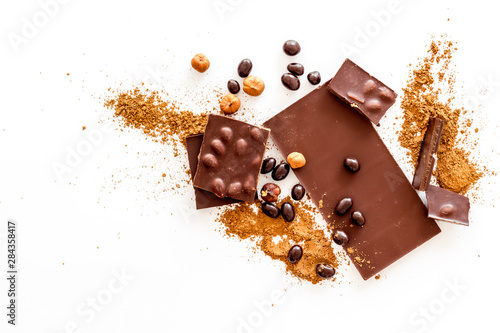 Pinturas sobre lienzo  Chocolate bars and nuts on white table background top view
