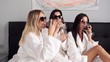 Tracking out shot of attractive girls in white bathrobes and sunglasses happily drinking red wine with breakfast in bed in hotel room