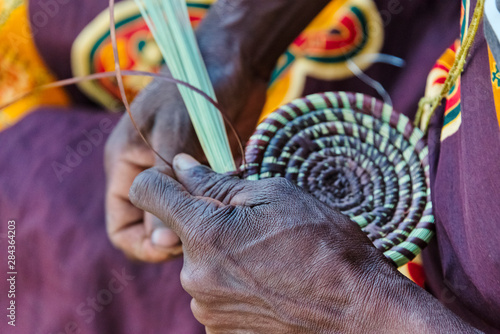 Fotografie, Obraz  Mbukushu tribe woman weaving grass cushion, Kwando Traditional Village, Zambezi