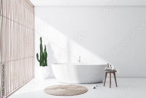 Fotografia  White and light wood bathroom interior with tub