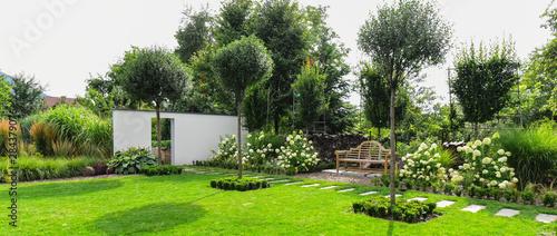 Staande foto Tuin Piękny ogród z drewnianą ławką