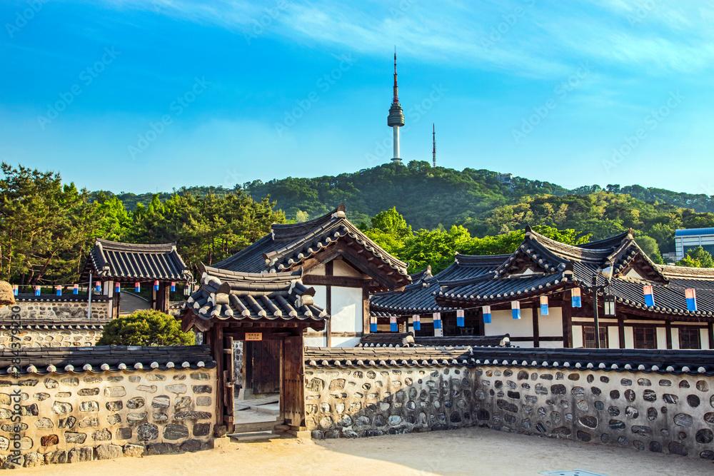 Fototapety, obrazy: Seoul, South Korea. Traditional Korean village courtyard of Namsangol Hanok with the YTN Seoul Tower (Namsan Tower or Seoul Tower) in the background.