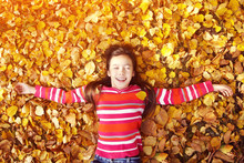 Beautiful Smiling Teenage Girl Lying On Yellow Leaves In Autumn. Top View.