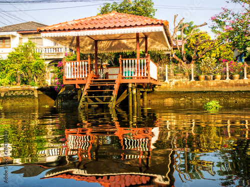 Vászonkép  Southeast Asia, Thailand, Bangkok, Homes in reflection along back canal