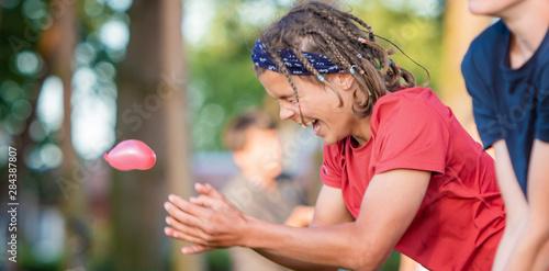 Obraz Summer camp, gry i zabawy , młodzież na świeżym powietrzy podczas wakacji latem,  szczęśliwy chłopak i zabawa z balonami  z wodą - fototapety do salonu