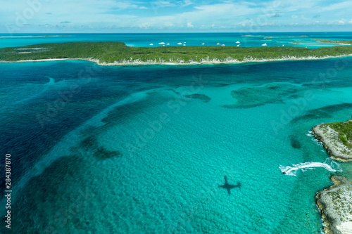Tuinposter Tropical strand Aerial photo looking down at the airplane's shadow, a jet ski and clear tropical water and islands in the Exuma Chain of islands the Bahamas near Staniel Cay.