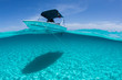 canvas print picture - A boat is anchored in the clear blue tropical waters off Staniel Cay, Exuma, Bahamas