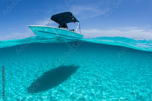 A boat is anchored in the clear blue tropical waters off Staniel Cay, Exuma, Bahamas
