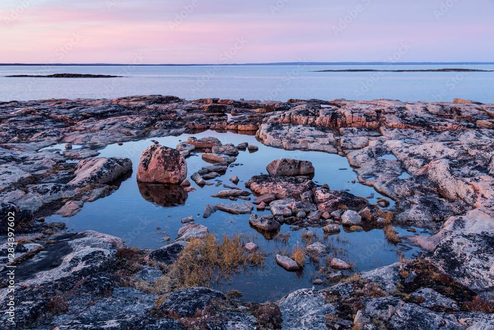 Canada, Nunavut, Territory, Setting midnight sun lights clouds above rocky coastline of Harbour Islands along Hudson Bay near Arctic Circle