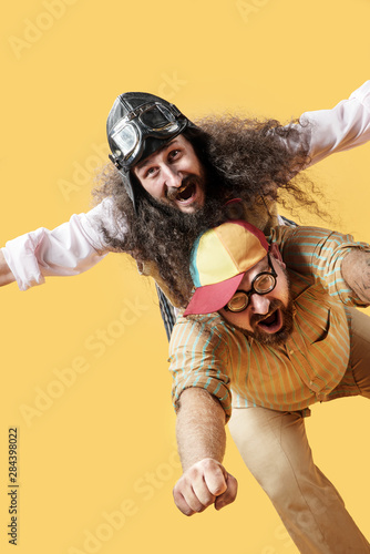 Платно Funny portrait of two friends acting flying
