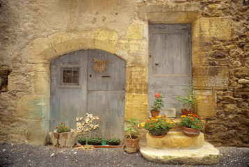 Fototapeta na wymiar France: St Come d'Oit, stone building with potted plants in front of blue wooden doors, August.